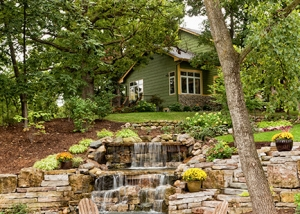 Peaceful Backyard Landscaping with Stone Waterfall and patio