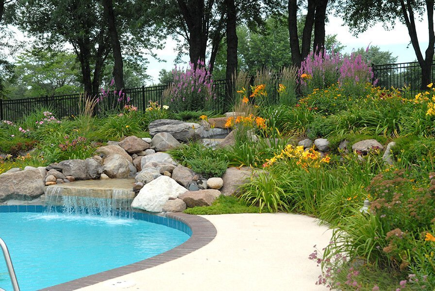 Outdoor pool and waterfall with boulders