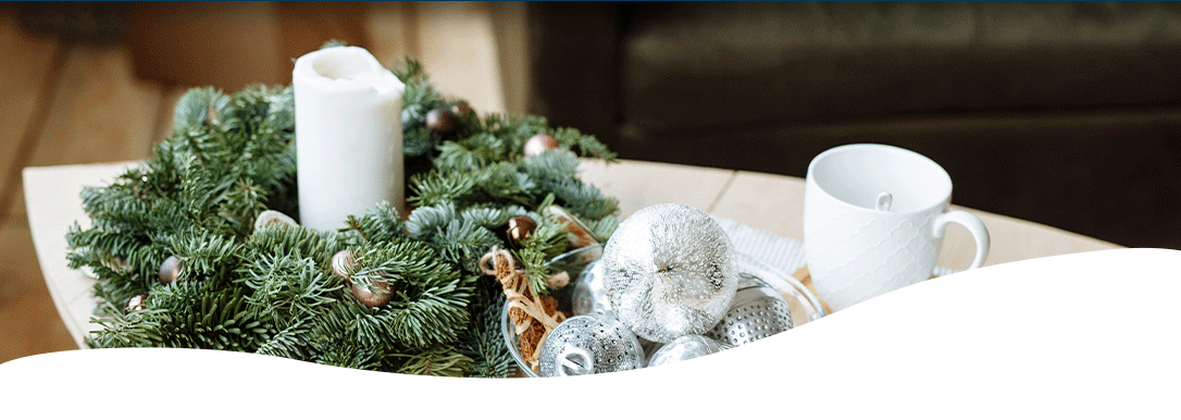 fresh greens decorated candle holder beside a glass bowl of silver ornament balls
